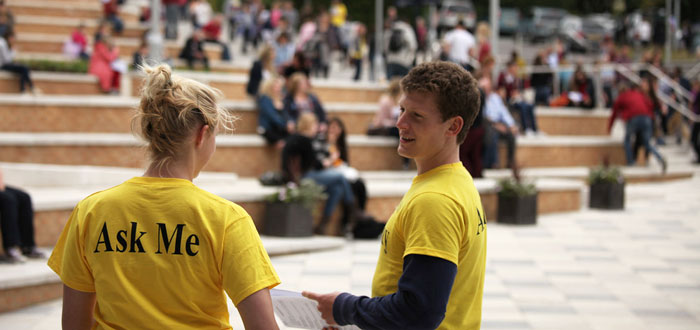 2 students with yellow T shirts on Piazza - Post offer Open Day