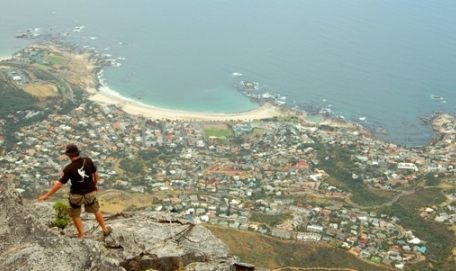 Hiker gazing out at coastal town and sea