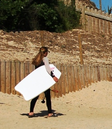 Girl walking with surfboard
